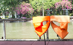 Orange life safety jackets dried on fence Royalty Free Stock Images