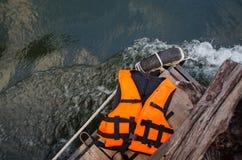 Life vest on wooden ground. Orange life vest on wooden background stock photo