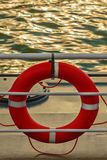 Orange lifebelt on a ship deck during sunset Royalty Free Stock Image