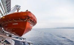 Orange Lifeboat Hanging Over Grey Water Stock Photo
