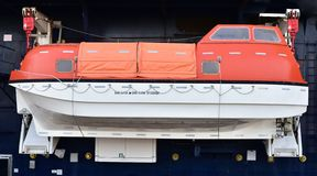Lifeboat of the passenger ship. Orange lifeboat for the quick escape included in the passenger ship stock photography