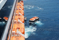 Orange lifeboats loading from liner in Croatia. Dubronik, Croatia - December, 20, 2007: Orange lifeboats, modern boats, for emergency evacuation loading for Stock Images