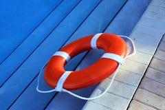 Orange Lifebuoy. A bright orange lifebuoy in a swiming pool Royalty Free Stock Image