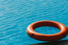 Orange lifebuoy in the blue water. Photo in the daytime Royalty Free Stock Photo