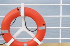 Orange lifebuoy emergency gear/ device/ equipment with reflective silver strips on cruise ship deck. Drowning/ overboard incident safety standards stock photography