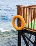 Orange lifebuoy hanging on a brown wooden pier against the blue Stock Image
