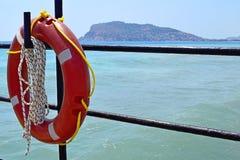 Orange lifebuoy hanging on a metallic fence. Lifebuoy hanging on a hook. Rescue on waters. Blue sea Stock Photos