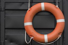 Orange lifebuoy hanging on the wall. Of a rescue station on a beach in Estonia royalty free stock photos