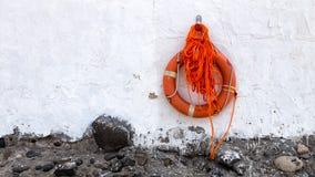 Orange lifebuoy hanging on white wall. Orange lifebuoy hanging on a rough wall, white plaster with black pebbles at the bottom Royalty Free Stock Photos