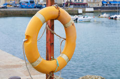Orange lifebuoy in harbor Stock Photos