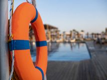 Orange lifebuoy near public swimming pool On a blurred background, a swimming pool is visible stock photos
