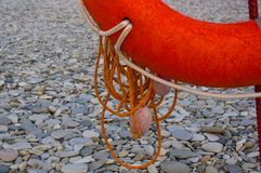 Lifebuoy on a sea beach. Orange lifebuoy on a pebbly sea beach, sunset Stock Photos