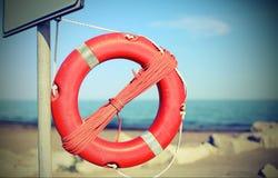 Orange lifebuoy for people near rocks at the sea Royalty Free Stock Photos