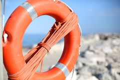 Orange lifebuoy for people near rocks at the sea Stock Images