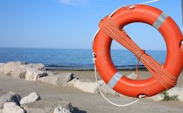 Orange lifebuoy for people near rocks at the sea in summer Royalty Free Stock Photos