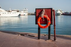 Orange lifebuoy on the pier on the background of yachts near the sea. Safety on the water and rescue from drowning. stock photography