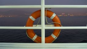 Orange lifebuoy at the railing of a cruise ship deck on dusk.  stock images