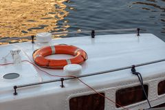 Orange lifebuoy on the roof of an old  boat. Red lifebuoy on the roof of an old pleasure boat stock photo