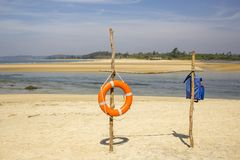 Orange lifebuoy ring and blue life vest on a bamboo stand on a sandy beach against the backdrop of the sea bay and green jungle royalty free stock photos