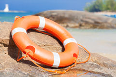 Orange lifebuoy on rocks at sea side. lifesaving Stock Image