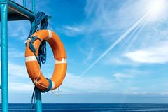 Orange Lifebuoy with Ropes on Lifeguard Chair. Orange and white life buoy with ropes hanging on a lifeguard chair with sea, blue sky, clouds and sun rays on stock photography