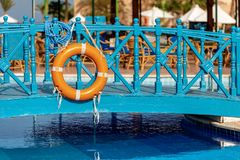 Orange Lifebuoy with Ropes in a Swimming Pool stock photo