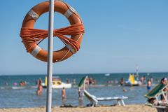 Rescue tires on the beach. Orange lifebuoy on the sandy beach and sea view Stock Image