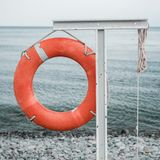 Orange lifebuoy on the sea coast. On cloudy day Royalty Free Stock Images