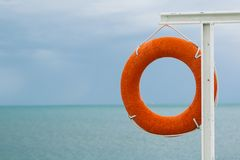 Orange lifebuoy on the sea coast. On cloudy day Royalty Free Stock Photography