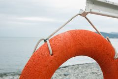 Orange lifebuoy on the sea coast. On cloudy day Stock Photography