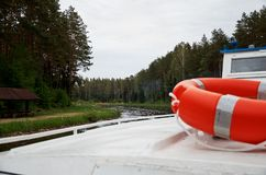 Orange lifebuoy on a ship sailing along the river near the forest. Stock Images