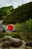 Lifebuoy at unusual place. Orange lifebuoy stand mounted on a rock at lake shore Royalty Free Stock Images