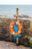 Orange lifebuoy on a stone wall rescue, blue rope, ocean shore Stock Photo