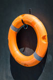 Orange lifebuoy on the wall near swimming pool. Orange lifebuoy on the dark wall near swimming pool Royalty Free Stock Images