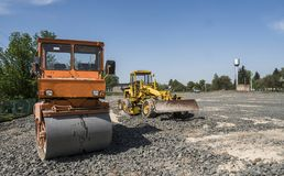 Orange light Vibration roller compactor standing on a stones at road construction and repairing asphalt pavement works royalty free stock images