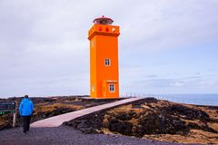 Orange lighthouse with human in the foreground stock photo