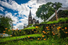 Orange lillies and St. Peters Roman Catholic Church, in Harpers Stock Photography