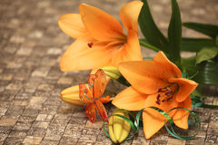 Orange lily. Flowers with decorations on a table Royalty Free Stock Photography