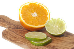 Orange and lime slices cut on a wooden board, isolated en white Royalty Free Stock Photos