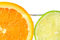 Orange and lime slices in water. With air bubbles on white background Royalty Free Stock Image
