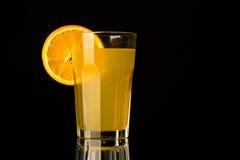Orange Limonade mit Stück der Orange im Glas auf schwarzem Hintergrund Stockbild