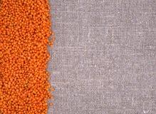 Orange Linsen auf einem Leinenhintergrund Stockfotos