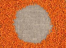 Orange Linsen auf einem Leinenhintergrund Stockbilder