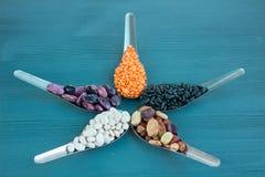 Orange linser, svart, vit, brunt, purpurfärgade bönor på blått trä Arkivbild