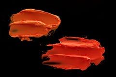 Orange lipstick smudge. D on a black isolated background Stock Image
