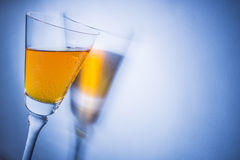 Orange liqueur into a glass. Multicolored reflections on the background Stock Photo