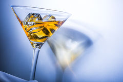 Orange liqueur into a glass. Multicolored reflections on the background Royalty Free Stock Photography