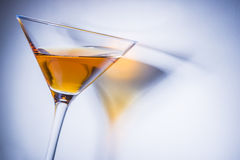 Orange liqueur into a glass. Multicolored reflections on the background Stock Image