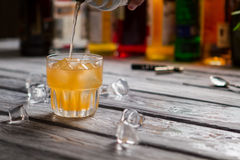 Orange liquid pours into glass. Royalty Free Stock Photography