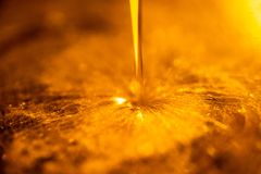 Orange liquid and viscous stream of motorcycle motor oil like a flow of honey close-up. royalty free stock photography